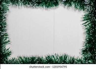 Christmas and New Year holiday background. Tinsel on white wooden table. Top view. Copy space. Flat lay.