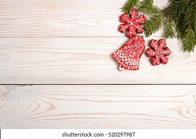 Christmas New Year holiday background. Red gingerbread cookies and fir branch tree on white table. Top view. Copy space