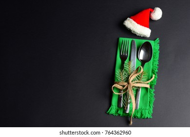 Christmas and New Year holiday background with cutlery and Santa Claus hat. Black creative background with a text space for restaurant or cafe.