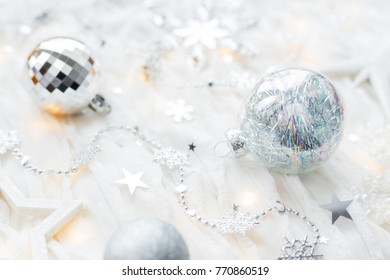 Christmas and New Year holiday background with decorations and light bulbs. Silver and white shining balls, snowflakes and star confetti.
