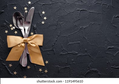 Christmas and New Year holiday celebration table setting on black background. Place setting for Christmas Dinner. Holiday Decorations. Decor. Top view. Copy space.