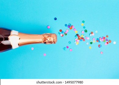 Christmas and New Year holiday festive background. Bottle of champagne and colored confetti over blue background. Flat lay, top view