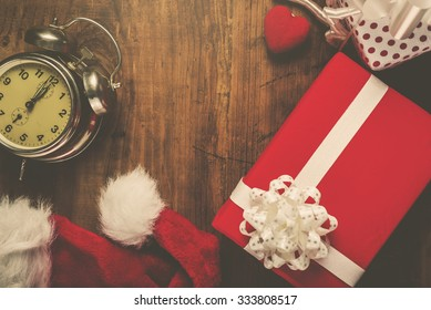 Christmas and New Year holiday, Santa Claus hat, presents, gifts and vintage clock at midnight, top view, retro filter toned image