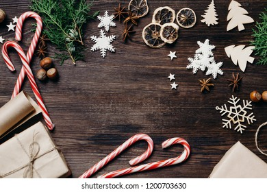 Christmas and New Year holidays atmosphere. Greeting card or poster template. Traditional festive decorations, presents and sweets at vintage wooden background, copy space.