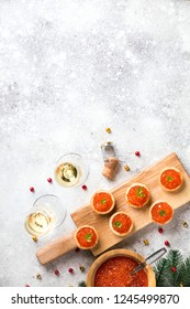Christmas and New Year holidays composition. Red Salmon Caviar in wooden bowl, Tartlets Festive Appetizer and champagne on  gray background.Copy space for Text.