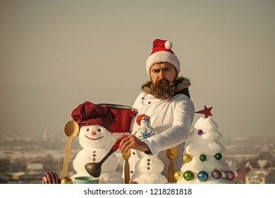 Christmas and new year holidays food. Unhappy hipster with ladle in white uniform. Cook, snowmen and snow xmas tree on blue sky. Cooking and diet concept. Man in santa hat ladling soup on winter day.