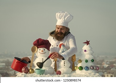 Christmas and new year holidays food. Happy cook, snowmen and snow xmas tree on blue sky. Cooking and diet concept. Hipster with ladle in white uniform. Man in chef hat ladling soup on winter day.