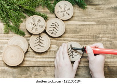 Christmas or New Year homemade pyrography toys. Wooden slice. Xmas decorations. Child makes gifts for relatives. View from above.