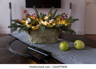Christmas or New Year illuminated basket  decoration on a table in front of TV with remote controls and apples