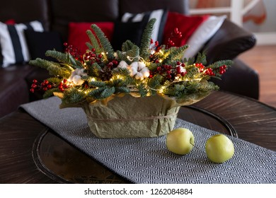 Christmas or New Year illuminated basket decoration, fir and red berries on a table in front of sofa with colorful pillows and apples