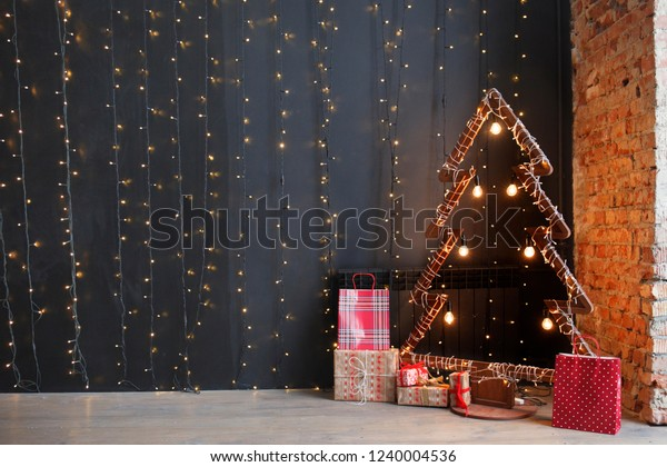 Christmas, New Year interior with black wall background, garlands, fir tree with lamps and Christmas gifts