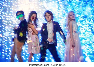 Christmas and New Year kid's party. Cool modern children sing and play electric guitar next to the speakers. Disco and lights.
