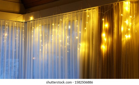 Christmas and New Year light decoration at home. Interior hanging sparkling lights decoration on window.