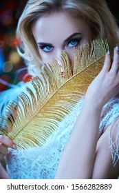 Christmas and New Year magic. Charming happy young woman in a festive evening dress holding a Golden feather. Lights around.