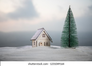Christmas and New Year miniature house in the snow in the sunlight. Little toy house on snow with tree. Festive background. Christmas decorations. Holiday and celebration concept.
