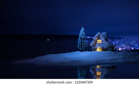 Christmas and New Year miniature house in the snow at night with fir tree. Little toy house on snow with tree and bokeh city lights on background. Christmas decorations. Holiday concept.