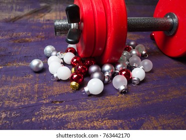 Christmas or New Year on a violet wooden background. Composition with dumbbells, for healthy lifestyle and sport