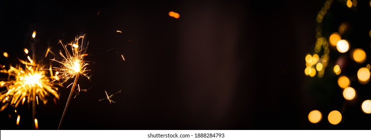 Christmas or New Year party sparkler with blurred gold lights on dark background. Festive Magic sparks lights for holiday poster, birthday or party concept.
