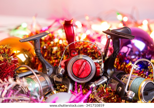christmas and new year a postcard for fishers and anglers. fishing reel on bright spangles and ball background with blur