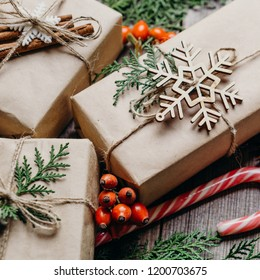 Christmas and New Year preparation. Gift boxes in craft paper and festive decorations, close up. DIY, winter holidays celebration and creativity concept