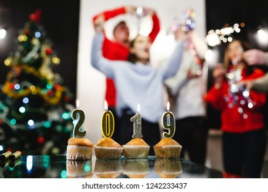 Christmas and New Year preparetions. Company of attractive happy young people celebrate clanging glasses and dancing around the Christmas tree. Candles with number of the year 2019 shine on the table