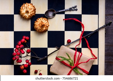Christmas or New Year present on a chessboard with coconut biscuits. Top view, copy space.
