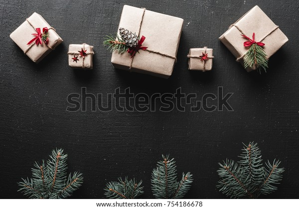 Christmas or New Year presents wrapped in paper and decorated with traditional Xmas twine and fir twigs on a black background