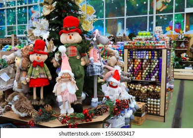 Christmas and New Year s toys in the store.  funny dolls in hats in a store. Festive winter Christmas trade, fair in a shopping center, mall.