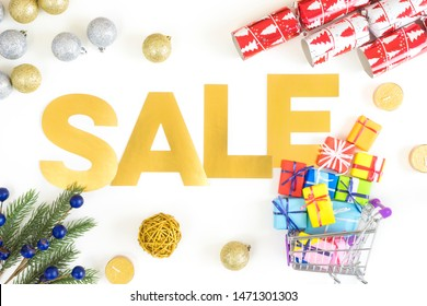 Christmas and New Year shopping concept with golden SALE words and christmas tree, gifts and ornaments. Flatlay.