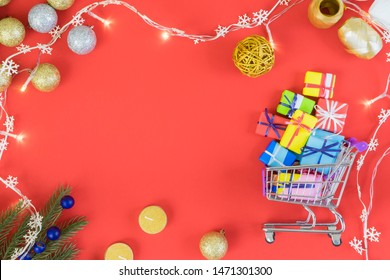 Christmas and New Year shopping template with christmas decorations and trolley filled with presents. Flatlay.