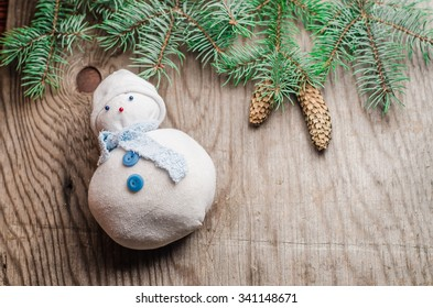 Christmas (New Year) sklad.Snihovyk decorating Christmas tree branches and cones on a wooden background