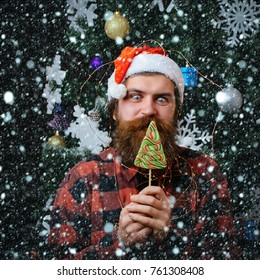 christmas new year snow concept Party celebration and blowjob. santa claus man in hat at decoration. Christmas man with beard on happy face and lollipop. Winter holiday xmas. New year guy lick candy