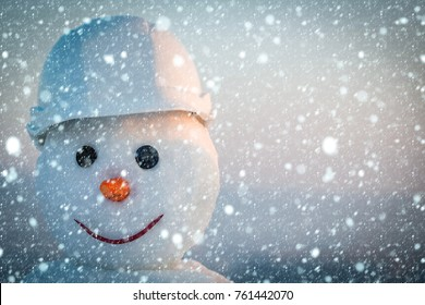 christmas new year snow concept New year snowman from snow in winter. Snowman builder in helmet. Happy holiday and celebration. Christmas or xmas decoration. Building and repair work., copy space