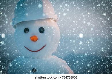 christmas new year snow concept Snowman builder in helmet. Happy holiday and celebration. Christmas or xmas decoration. New year snowman from snow in winter. Building and repair work.