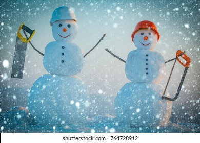christmas new year snow concept Building and repair work. Happy holiday and celebration. New year snowman from snow with saw. Snowman builder in winter in helmet. Christmas or xmas decoration.