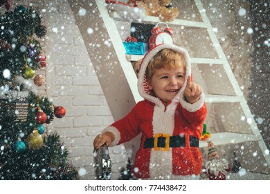 christmas new year snow concept Santa claus kid decorating Christmas tree.. Christmas happy child with gift clock. New year small boy at decoration toy. Winter holiday and vacation. Xmas party