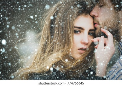 christmas new year snow concept Sexy man and girl with fashion makeup and long hair touching each other with love and tenderness. Young couple of heterosexual lovers outdoors
