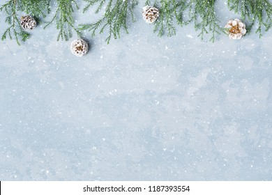 Christmas and New Year snowy background. Green twigs and cones border. Blue copy space, top view. Winter holidays.