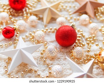 Christmas and New Year star decorations on white knitted background. Metal light bulbs with delicate pattern, golden beads, red balls.