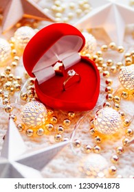 Christmas and New Year star decorations on white knitted background. Red heart gift box with engagement golden ring, metal light bulbs with delicate pattern, beads.