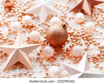Christmas and New Year star decorations on white knitted background. Metal light bulbs with delicate pattern, pale beige and red beads.
