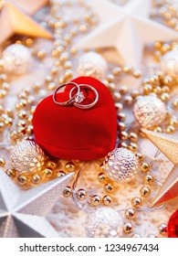 Christmas and New Year star decorations on white knitted background. Red heart gift box with wedding diamond rings, metal light bulbs with delicate pattern, golden beads.