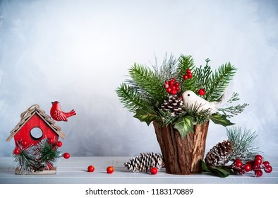 Christmas and New year still life with festive decor on the wooden background. Christmas bunch and bird house