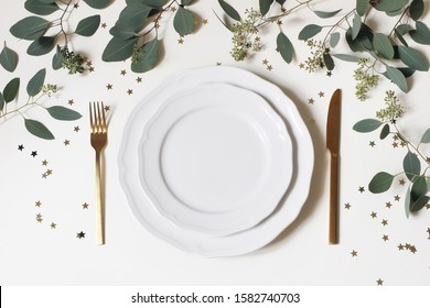 Christmas, New Year table place setting. Golden cutlery, porcelain plate, eucalyptus branches and golden confetti stars isolated on white background. Winter holidays background. Flat lay, top view.