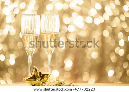 christmas and new year theme background with champagne flutes against a gold glitter background