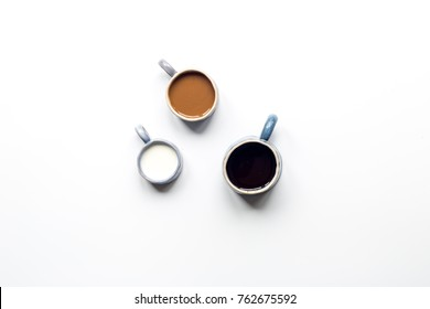 Christmas and new year theme. Blue ceramic cups of milk, black coffee and coffee with milk on white background flat lay.