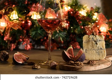 Christmas   and new year theme: Cheese roquefort with figs,nuts  and a wineglass of red wine on a wooden background