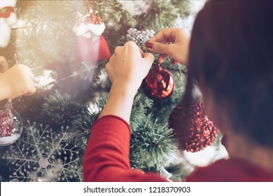 Christmas and new year theme young woman decorating christmas tree holding bauble at home back view close-up