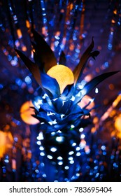 Christmas and new year tree creative idea and inspiration. A fresh real natural pineapple decorated with rice lights and glowing garlands or lamps