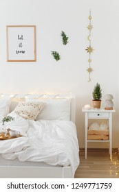 Christmas or new year winter home interior decor. Holiday decorated room. White stylish cozy scandinavian bedroom with little christmas tree, coniferous twigs or pine branches and led garland lights.